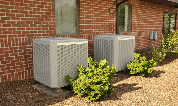 Two air conditioning units in Manchester, MO against a brick building.
